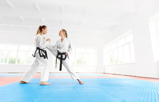 Young karate girl helping to her partner stretching leg before training.