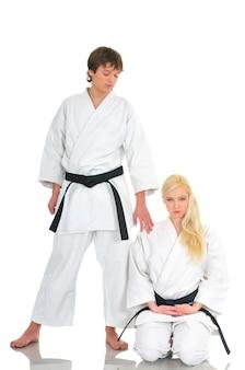 若い空手才能のある魅力的な女の子と若い男は、白い背景に目を閉じて着物のスーツを着て膝の上に座っています。