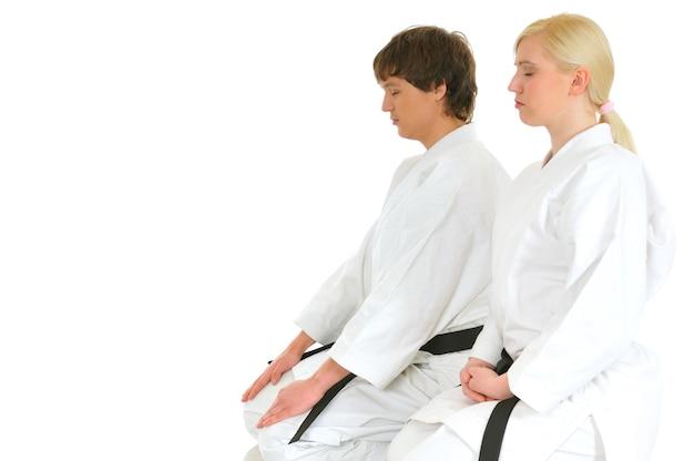 若い空手才能のある魅力的な女の子と若い男は、白い目を閉じて着物のスーツを着て膝の上に座っています