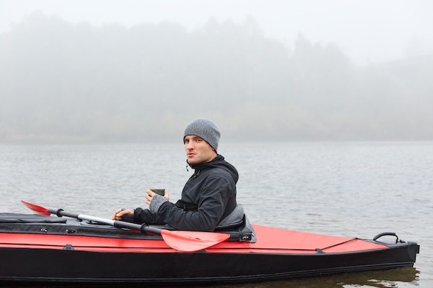 Young kayaker sitting in canoe in middle of river or lake looking in distance and drinking hot coffee , wearing jacket and cap, foggy morning, active rest.