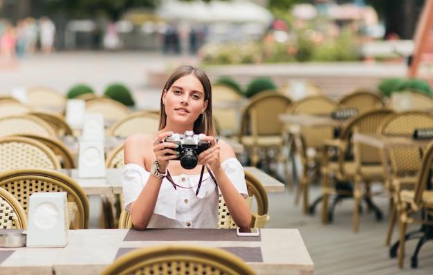 若い熱心な女性が屋外カフェのテーブルに座っている間彼女の手で古いレトロなカメラを保持しています。
