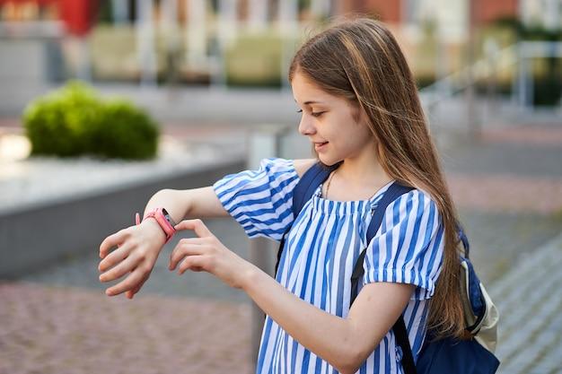 어린 소녀는 분홍색 smartwatch.near 학교로 부모님과 영상 통화를 합니다.