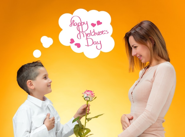 Young kid giving red rose to his mom. happy mothers day concept
