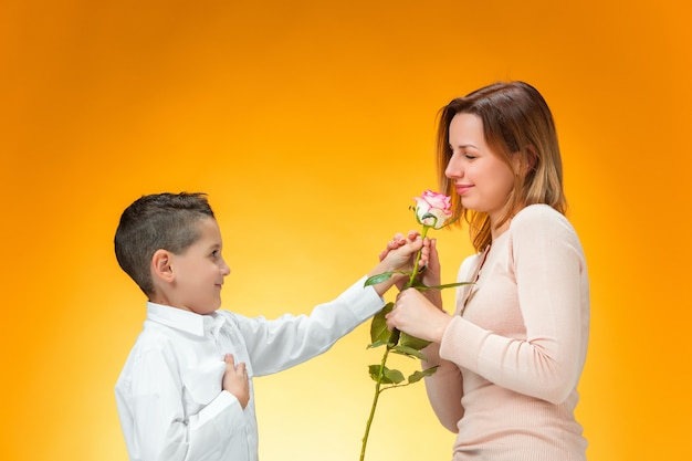 Young kid giving red rose to his mom