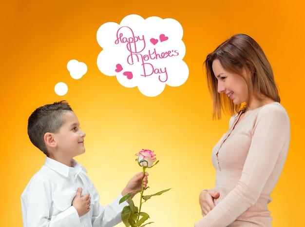 赤いバラを彼のお母さんに与える幼い子供。幸せな母の日のコンセプト