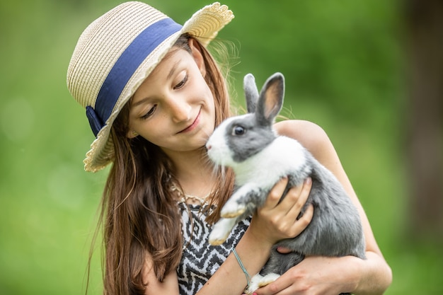 어린 아이가 회색 토끼를 손에 들고 행복하게 놀고 있습니다.