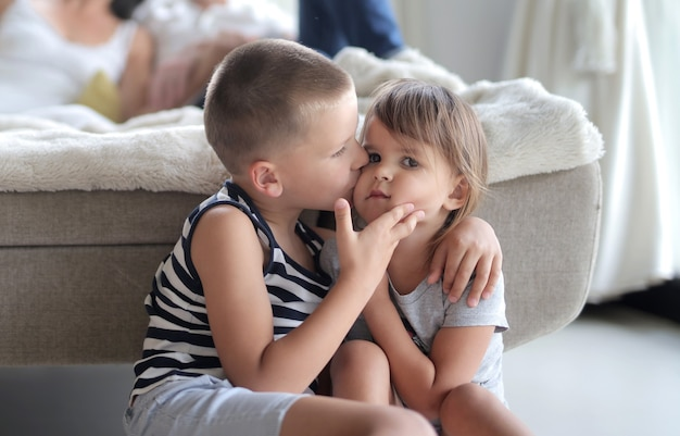 Young kid kissing his sister's cheek under the lights
