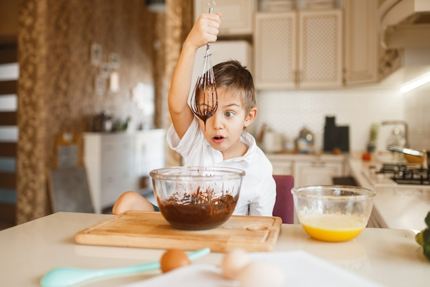 ボウルに溶かしたチョコレートを混合する子供