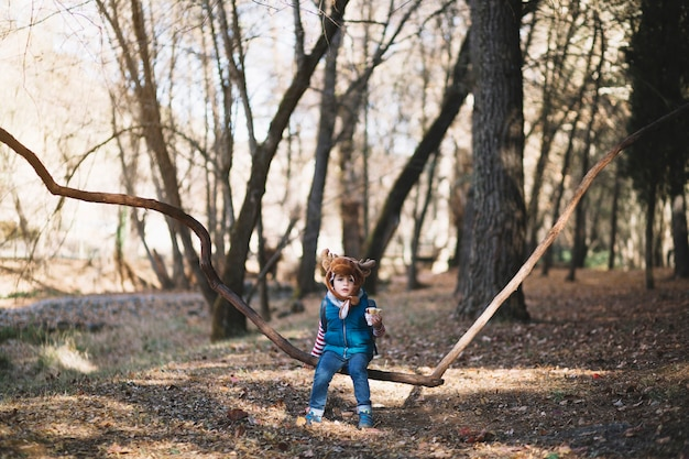Young kid sitting on branch