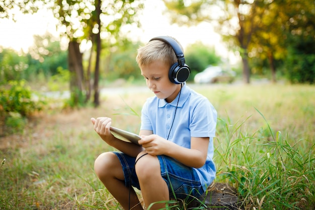 Young kid sitting in the forest wearing headphones and playing a game on tablet pc.