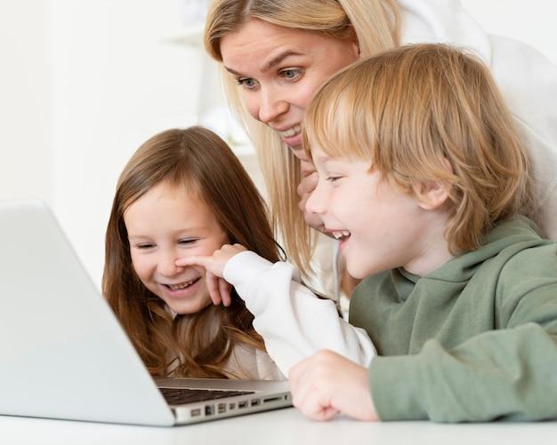 Маленькие дети и мать с помощью ноутбука