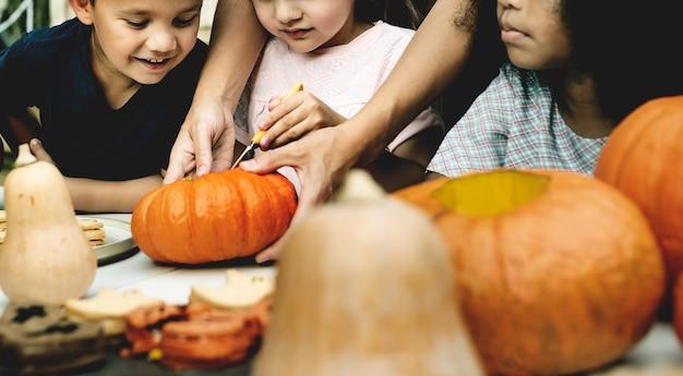 Young kids carving halloween jack lanterns