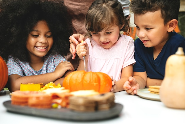 Young kids carving halloween jack-o'-lanterns