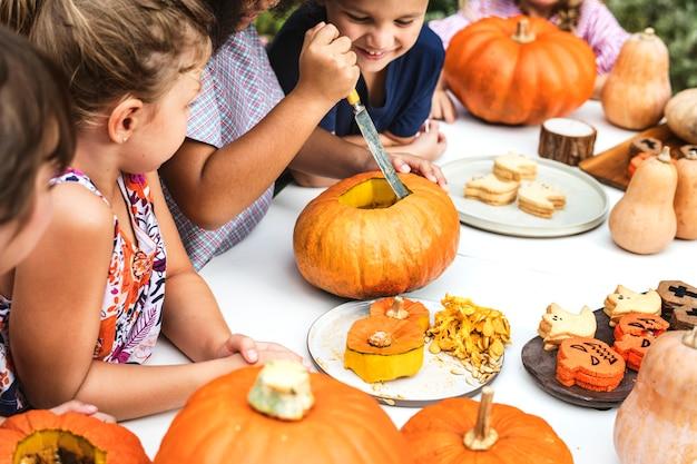 Young kids carving halloween jack-o-lanterns