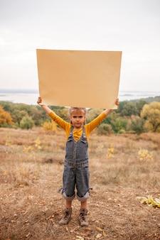 秋の自然にポスターを保持している若い子供たち