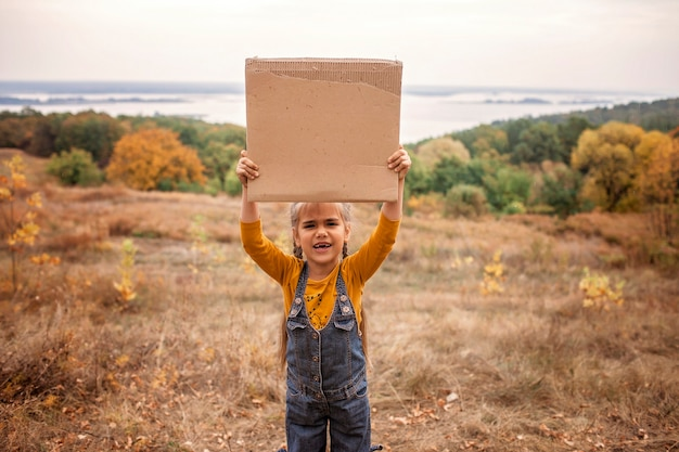 Young kids holding a poster over autumn nature