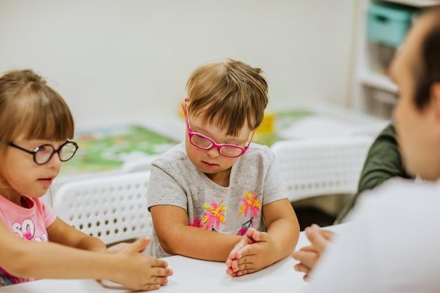 흰색 책상이있는 방에서 공부하고 노는 다운 증후군을 앓고있는 어린 아이들