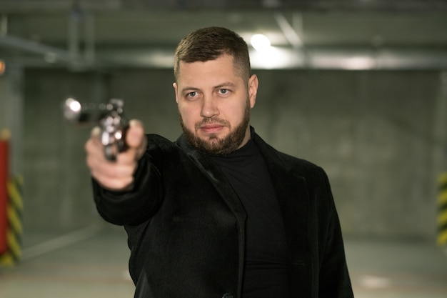 Young killer or agent in black jacket and t-shirt directing handgun on victim or criminal ready to shoot