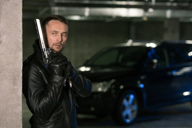 Young killer or agent in black leather jacket and gloves holding handgun while standing by corner and waiting for victim