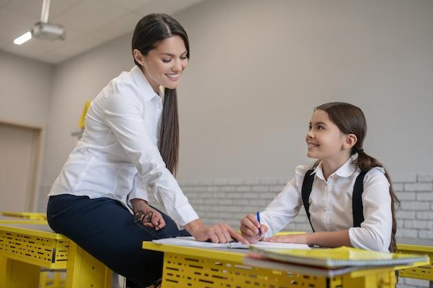 学校の教室で気配りのある楽しい女子高生を教える若い親切な笑顔の先生