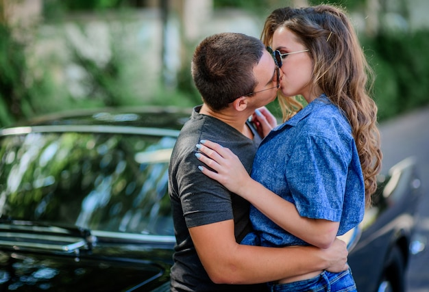 Young kissing couple dressed in a casual style stands before an old sport retro car
