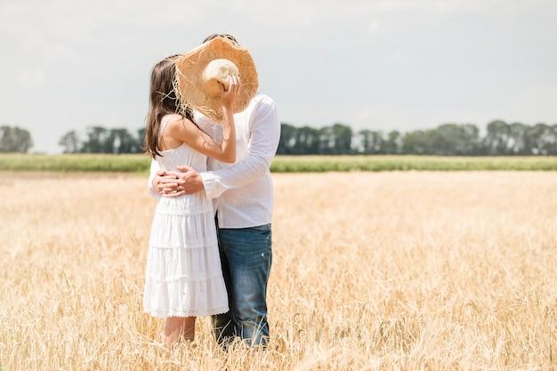 Молодая пара поцелуев прячется за шляпой в поле