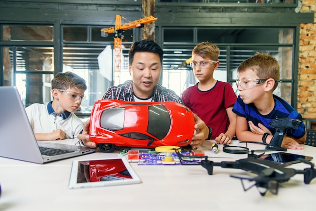 Young korean man of electronics engineer with young children using screwdriver to disassemble robotic machine at the table in the modern school. slow motion