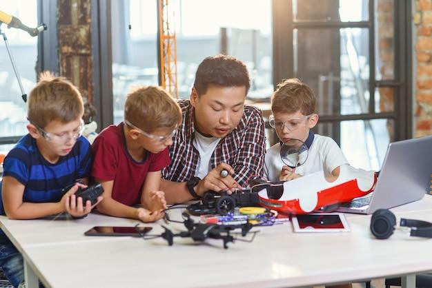 現代の学校のテーブルでロボットマシンを分解するためにドライバーを使用している幼児を持つ電子工学者の若い韓国人男性。スローモーション
