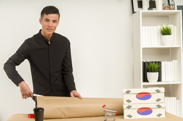A young korean man in an office packs a postal parcel gift draw for mailing.