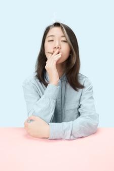 스튜디오에서 테이블에 앉아있는 동안 시가 흡연 젊은 한국 여성. 트렌디 한 색상