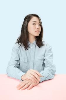 スタジオのテーブルに座って葉巻を吸う若い韓国人女性。