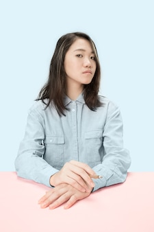 Giovani donne coreane di fumare il sigaro mentre è seduto al tavolo in studio.