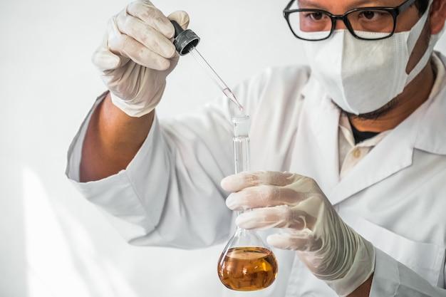 Молодой лаборант готовит прибор для химического лабораторного эксперимента в лаборатории