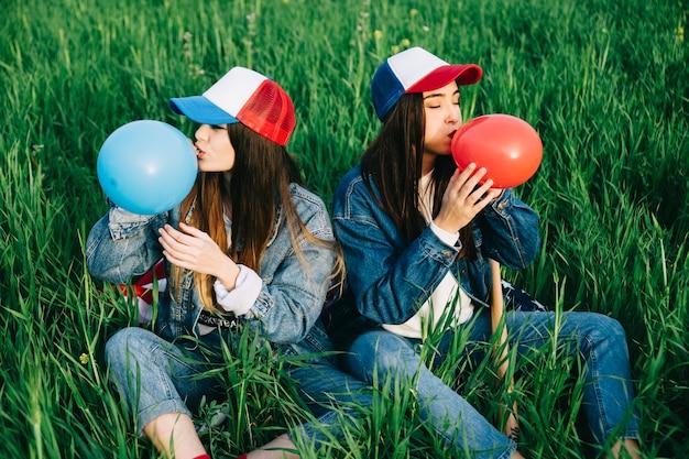 푸른 잔디에 컬러 풍선을 불고 젊은 숙 녀