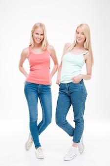 젊은 숙녀는 티셔츠와 청바지 포즈를 입고. 흰 벽 위에 절연. 앞을보고.