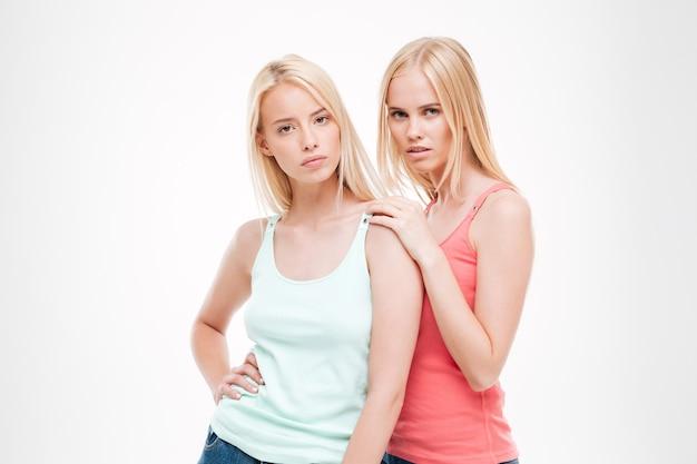 젊은 숙녀는 티셔츠와 청바지 포즈를 입고. 흰 벽에 절연