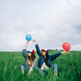 Young ladies having fun in summer field with different colors balls