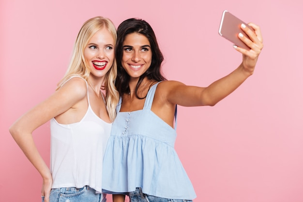 Young ladies making selfie and smiling isolated