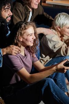 週末の夕方、家でゲーム機をしている若い女性が、カジュアルな服装で余暇を楽しんでいます。趣味、ゲーム、人々のライフスタイルのコンセプト