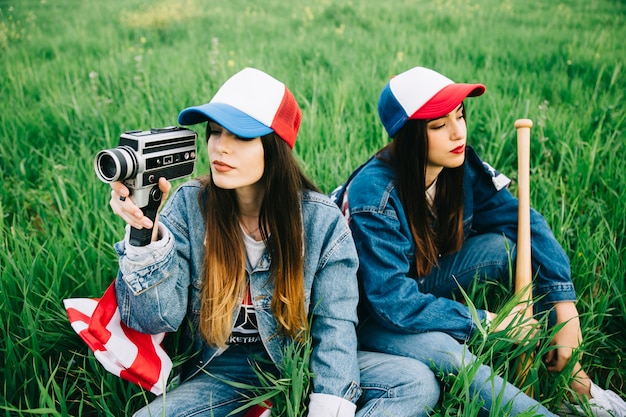 Young ladies sitting on green grass in colored caps
