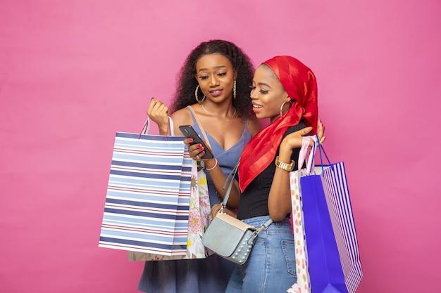Молодые дамы просматривают что-то на мобильном телефоне, неся сумки для покупок