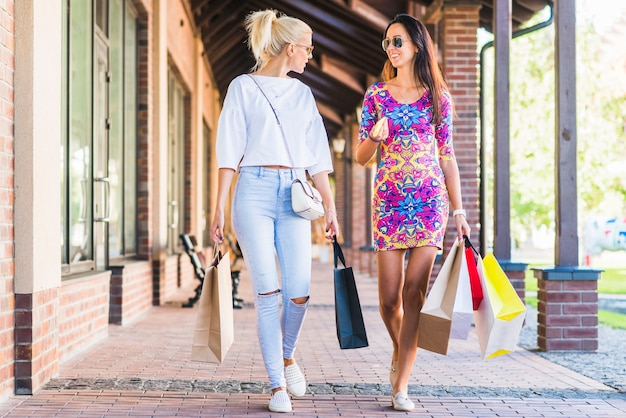 Young ladies with bags talking and going on shopping street