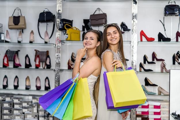 靴屋でポーズをとって買い物袋を持つ若い女性