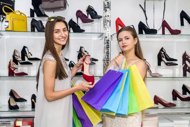 Молодые дамы с хозяйственными сумками позируют в обувном магазине