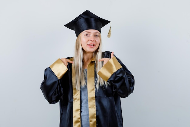 Young lady in academic dress pointing herself and looking proud