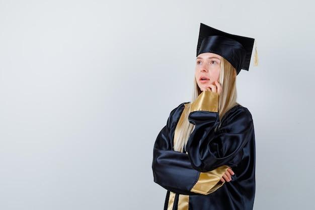 Giovane donna in abito accademico in piedi in posa di pensiero e guardando pensierosa