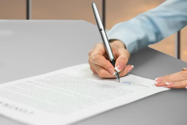 Документ, подписывающий руку юной леди. предприниматель, писать за столом. ставлю подпись серой ручкой. выбор карьеры.