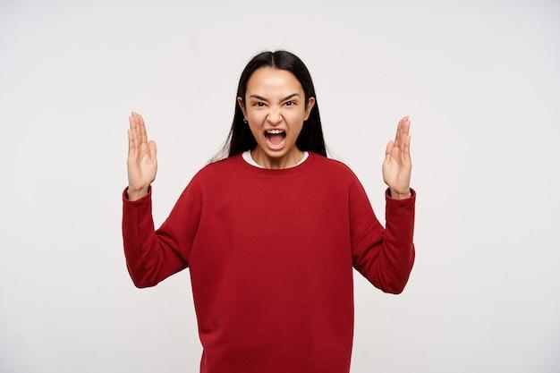 若い女性、暗い長い髪の怒っているアジアの女性。赤いセーターを着て、手を上げてイライラして叫ぶ。十分、これにうんざりしている。白い背景の上に分離されたカメラで見て