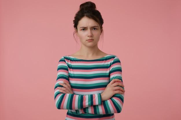 若い女性、怒っている、ブルネットの髪とパンを持つ真面目な女性。ストライプのブラウスを着て、胸に手を組んでください。感情的な概念。パステルピンクの壁に分離