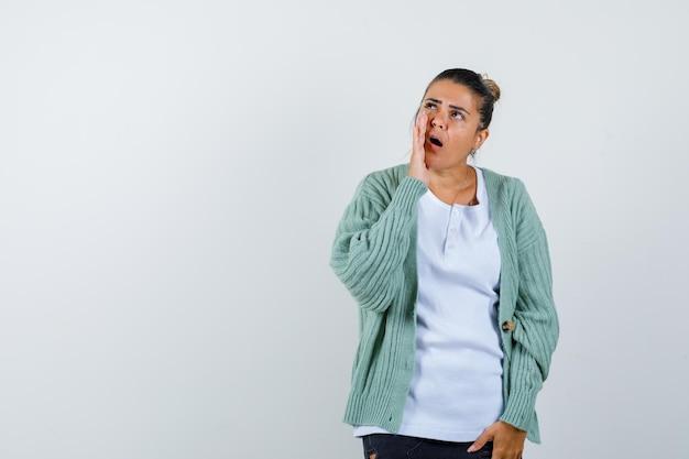 Tシャツ、ジャケットで何かを発表し、自信を持って見える若い女性
